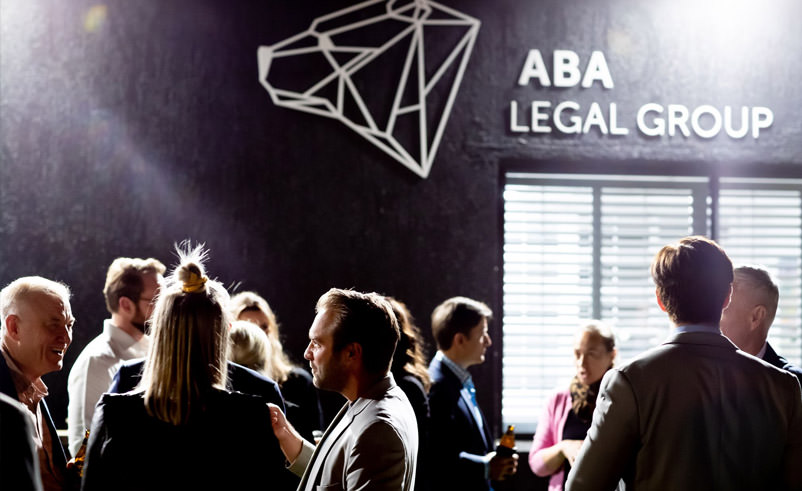 Brand Refresh Launch Event. Image of people mingling at brand refresh launch event in front of ABA Legal Group logo sign.
