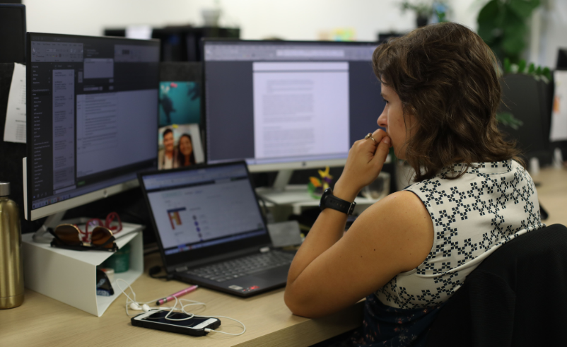 Small Business Grants. Image of Sofia sitting at her desk in front of two monitor screens and a laptop.